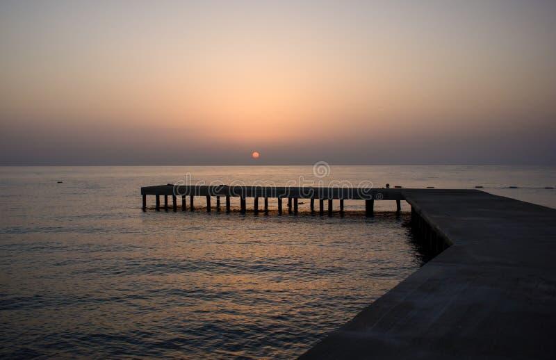 Bakgrund med den gamla träpir i havet på solnedgången royaltyfria bilder