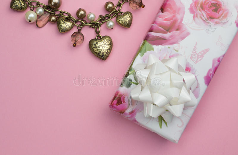 Bakgrund med den guld- hjärta- och pärlahalsbandet, slågen in rosa gåva royaltyfria foton