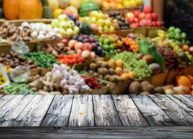 Bakgrund med den tomma trätabellen och blured frukter och vegetab arkivfoto