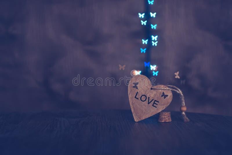 Bakgrund med en trähjärta- och fjärilsbokeh På hjärtan av ordförälskelsen royaltyfri bild