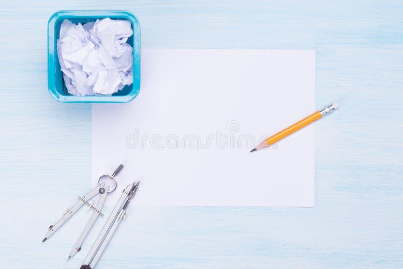 bakgrund med ett ställe för att skriva, på ett vitt ark, på som lämnas en soptunna för utkast och spridda hjälpmedel för diagram royaltyfria bilder