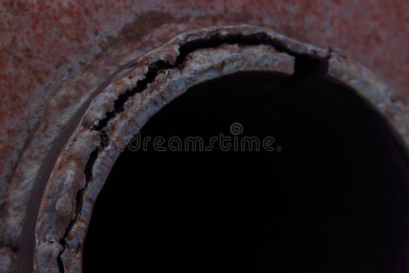 Bakgrund med ett svart hål och ärr av svetsning på en rostig grov metallyttersida fotografering för bildbyråer
