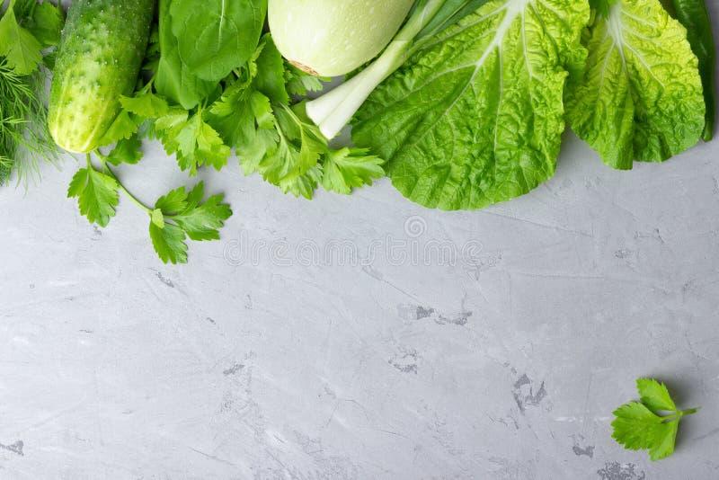 Bakgrund med gröna grönsaker, sallad, gurkan, salladslöken och zucchinin på överkant för grå färgstentabell royaltyfri foto