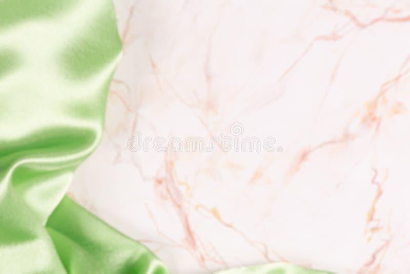 Bakgrund med grönt siden- tyg på ljus marmor arkivbild