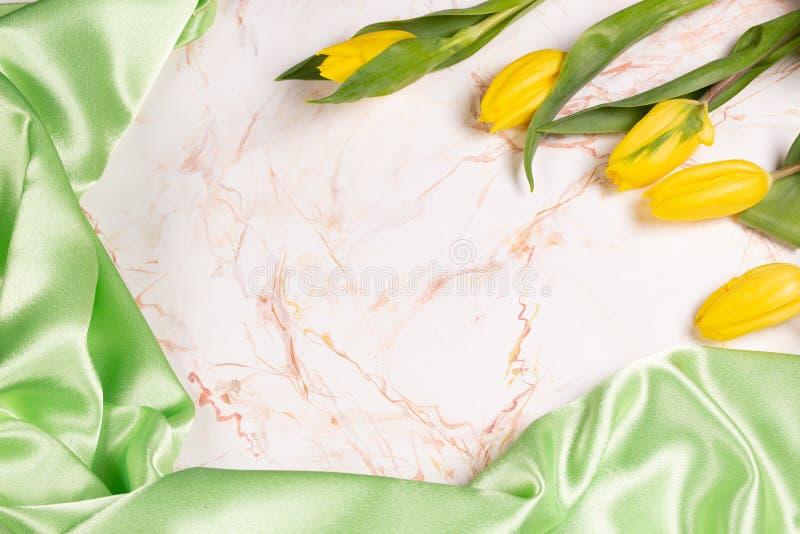 Bakgrund med grönt siden- tyg på ljusmarmor och gula tulpan royaltyfri fotografi