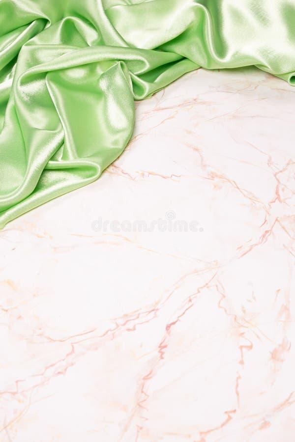 Bakgrund med gr?nt siden- tyg p? ljus marmor arkivfoton
