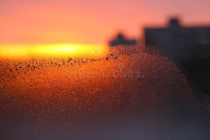 Bakgrund med is, morgonsolljus och konturer av hus på exponeringsglas arkivfoto
