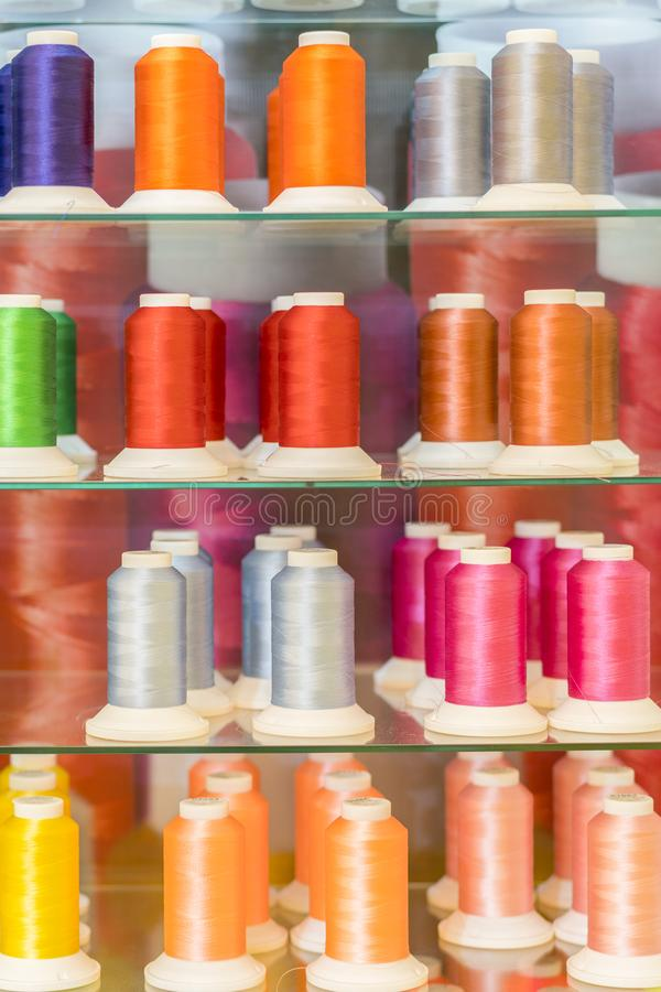 Bakgrund med mycket färgrika spolar med trådar Spolar staplas i tre rader, en på annan Spolningen är oregelbunden royaltyfri foto