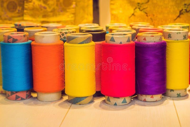 Bakgrund med mycket färgrika spolar med trådar Spolar staplas i tre rader, en på annan Spolningen royaltyfria foton
