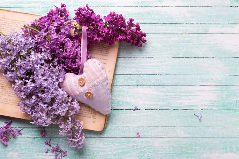 Bakgrund med nya lila blommor på den öppen tappningboken och honom arkivfoton