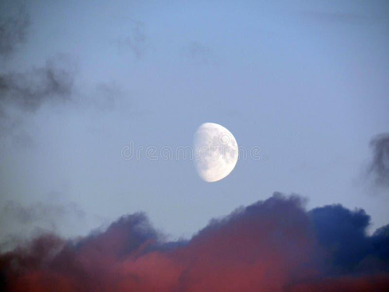 Bakgrund med resningmånen ovanför rosa solnedgångmoln arkivbilder