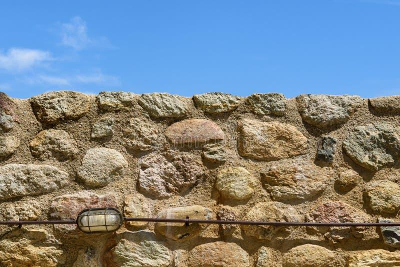 Bakgrund med stenväggen och blå himmel arkivbilder