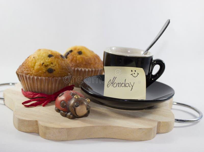 Bakgrund med vassi, kopp, muffin, nyckelpiga och lycklig måndag ` s c arkivfoto