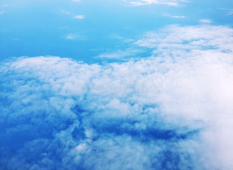 Bakgrund med vit f?rdunklar p? bl? himmel arkivfoto