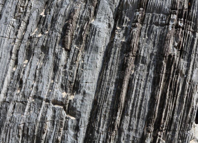 Bakgrund p? basen av texturen av vaggar Grå färgstenyttersidan med benägna vertikala band red ut royaltyfri bild