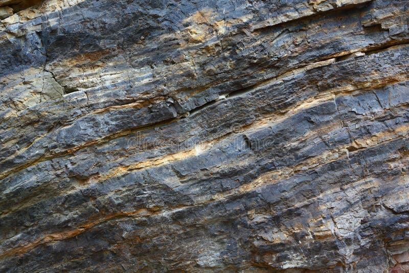 Bakgrund p? basen av texturen av vaggar Svart och röd sten med att slutta lager och sprickor royaltyfria foton
