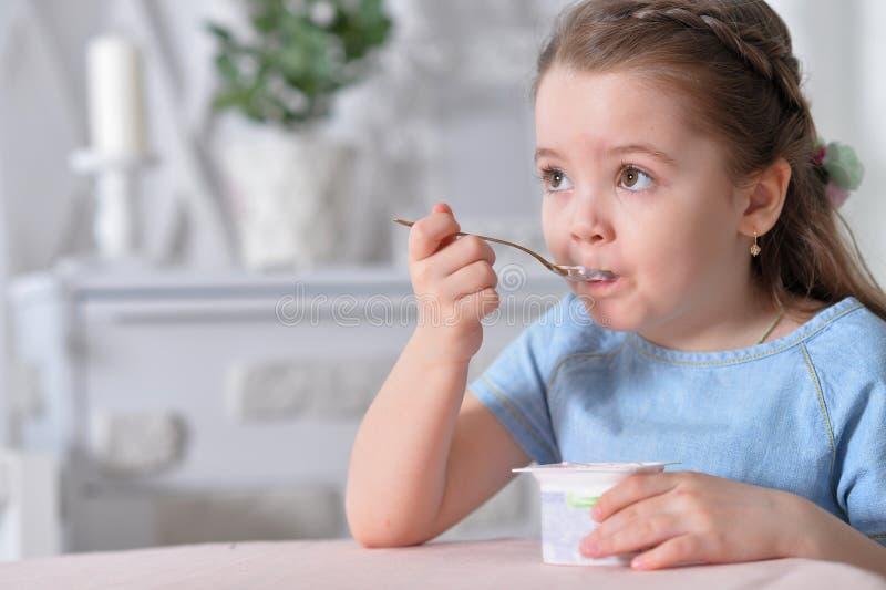 bakgrund som äter flickan som isoleras little vit yoghurt arkivfoto