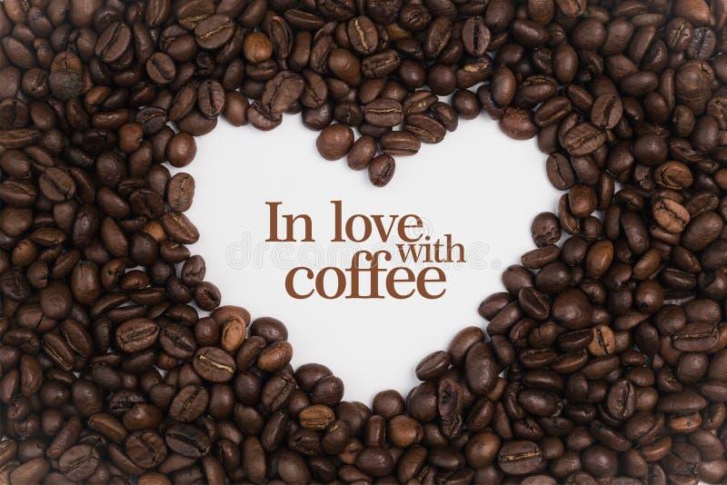 Bakgrund som göras av kaffebönor i en hjärtaform med meddelande` som är förälskad med kaffe`, royaltyfria foton