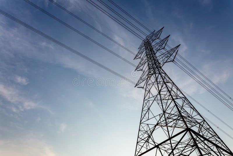 Bakgrund till elstolpe med högspänningskoppel royaltyfri foto
