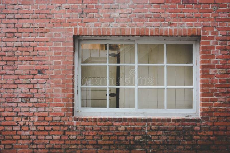 Bakgrund till gammal röd tegelvägg med klassisk vit ram av trä och streck med glaspaneler, kopieringsutrymme arkivfoton