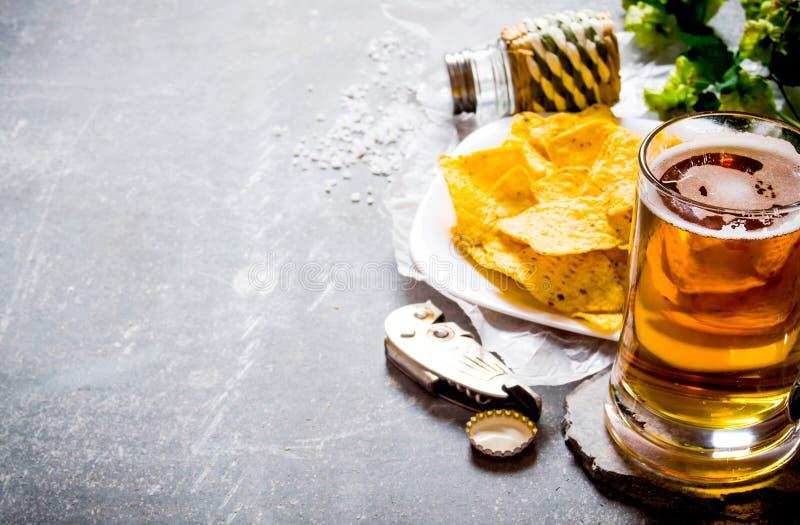 bakgrundsöl innehåller lutningingreppet Öl och chiper på gammal stenbakgrund arkivbilder