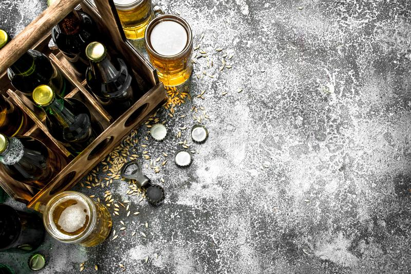 bakgrundsöl innehåller lutningingreppet Nytt öl i exponeringsglas och en gammal ask royaltyfri bild