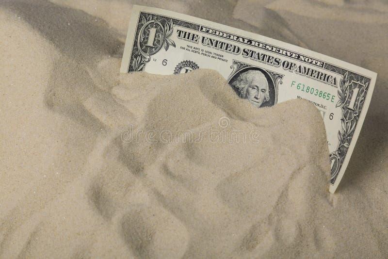 bakgrundsbegreppet bantar guld- äggfinans En dollarsedel i sanden royaltyfri foto
