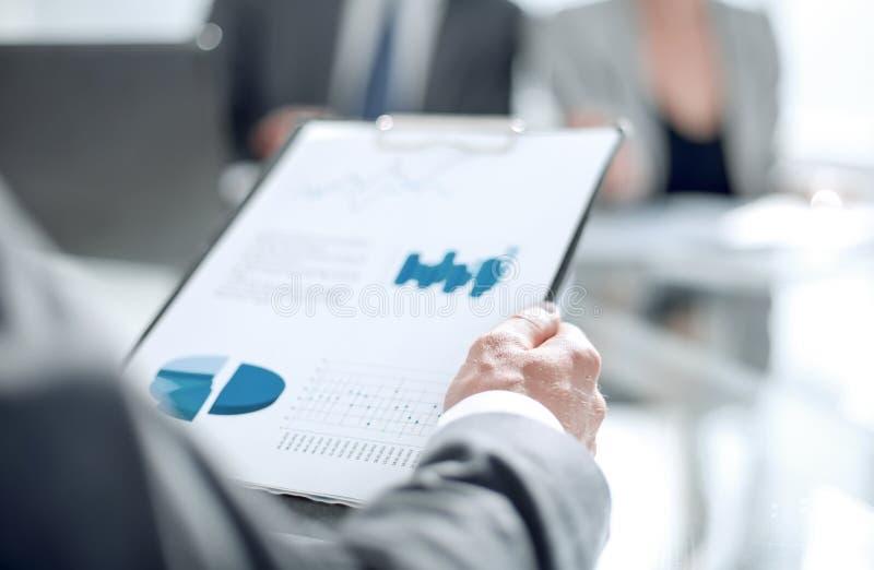 Bakgrundsbild av en affärsman som kontrollerar finansiella dokument arkivfoto