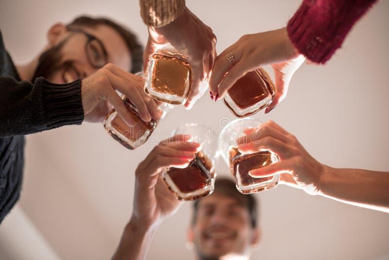 Bakgrundsbild av ett exponeringsglas av fruktsaft i händerna av de unga paren royaltyfria bilder