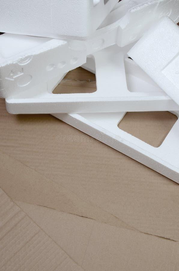 Bakgrundsbilden med beigea papppappers- och polystyrenaskar disgarded som rackar ner på Begreppet av uppackning av nya hem- anord arkivfoton