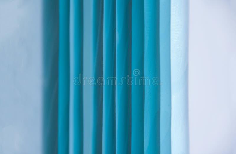 Bakgrundsblått rullar gardiner på en vit bakgrund royaltyfri fotografi