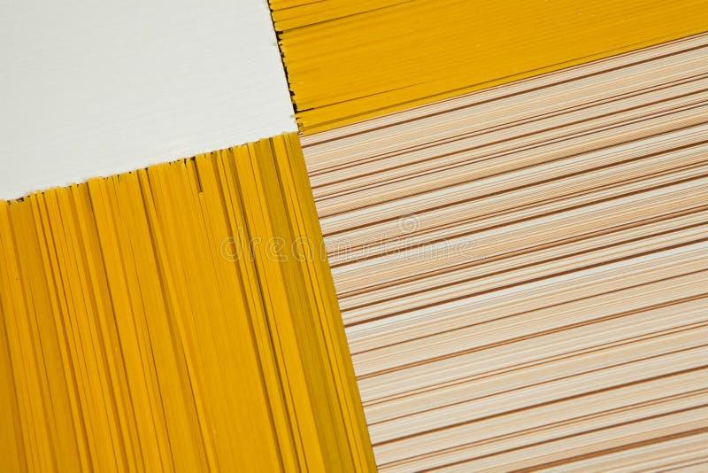 bakgrundsborrningen isolerade ingen spagettiwhite Gul lång spagetti på svart bakgrund Tunn pasta som är ordnad i rader italiensk  arkivbild