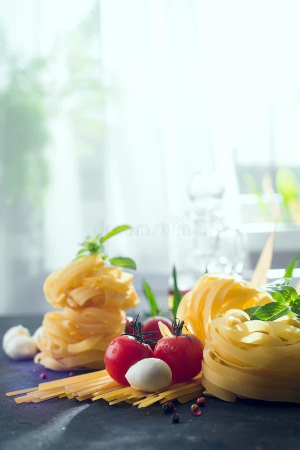 bakgrundsCherryingredienser isolerade white för pastaspagettitomat Körsbär-tomater, spagettipasta, basilika och kryddor på stenta royaltyfri foto