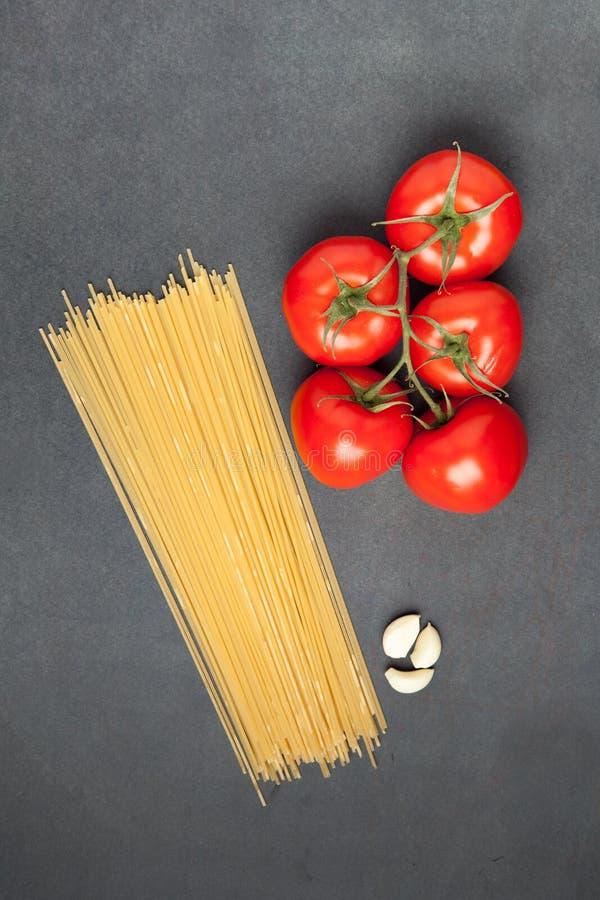 bakgrundsCherryingredienser isolerade white för pastaspagettitomat Tomater, spagettipasta och vitlök, på den mörka grungebakgrund arkivbilder