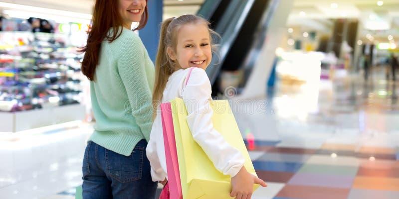 bakgrundsfamilj som isoleras ?ver shoppingwhite Litet barn som rymmer shoppingpåsar i stadsgalleria royaltyfri bild
