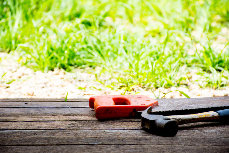 Bakgrundshantverkarehjälpmedlet och den gamla hammaren med såg på träbakgrund och utomhus- sikt Bakgrund för snickare och reparat arkivfoton