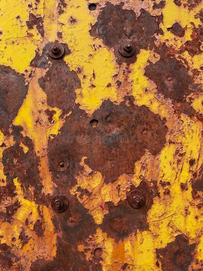 Bakgrundsjärnbultar på den rostade metallväggen med skalning av gul målarfärg royaltyfri bild