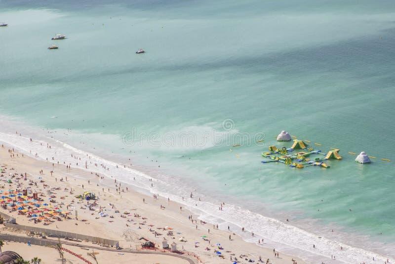 Bakgrundslandskapstrand i den Dubai marina med feriehandelsresande och golfen arkivbild