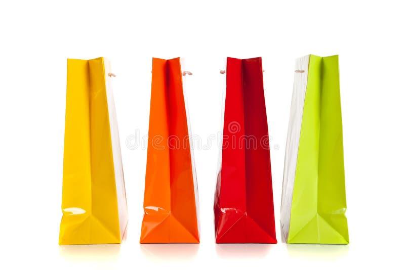 bakgrundspåsar färgade mång- shoppingwhite arkivfoton