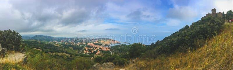 Bakgrundspanoramautsikt av staden av Collioure och fästningen på berget, från vägen till fästningen royaltyfria bilder