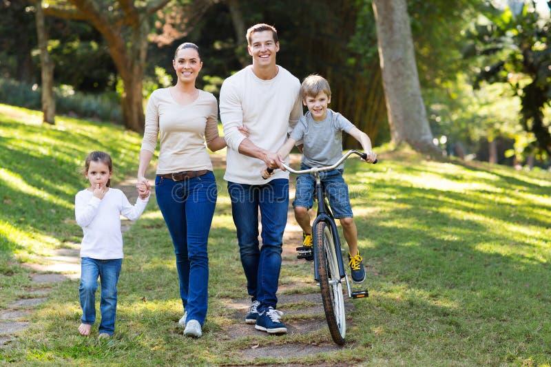 bakgrundspojke som omfamnar familjfaderflickan hans små fru för damm för manmoderpark arkivfoton
