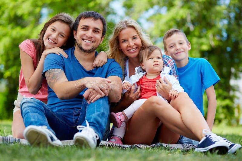 bakgrundspojke som omfamnar familjfaderflickan hans små fru för damm för manmoderpark royaltyfri bild