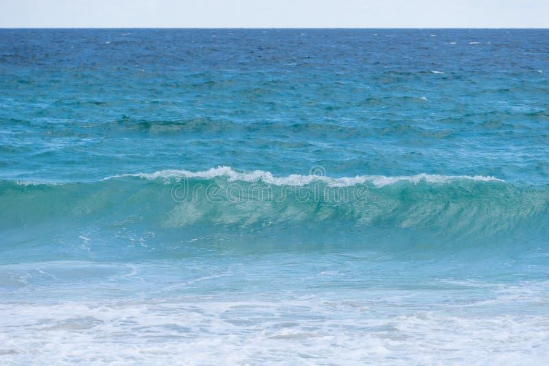 Bakgrundssuddighet och den kraftiga vågen bryter längs kusten arkivbilder