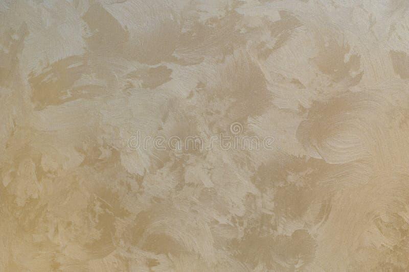 Bakgrundstextur av beigea guld- murbrukväggar arkivfoton