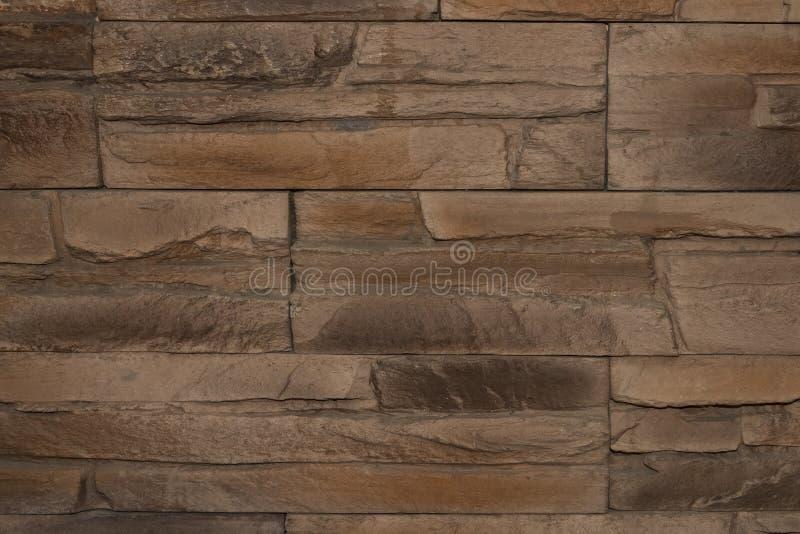 Bakgrundstextur av en gammal antik brun vägg som göras av den naturliga stenen royaltyfria foton