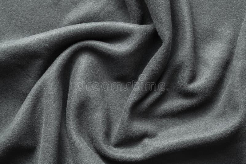 Bakgrundstextur av mörkt - grå ullbeklädnad arkivfoton