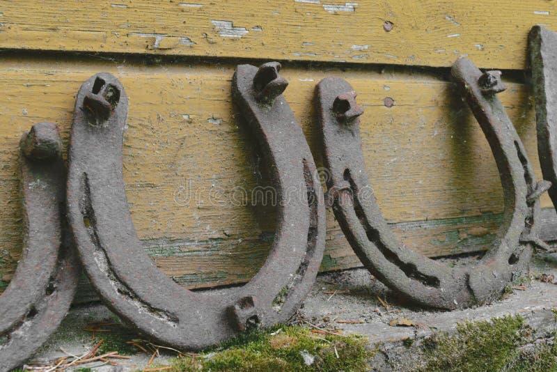 Bakgrundsyttersida av mycket gamla och rostiga hästskor som förläggas nära väggen royaltyfri foto