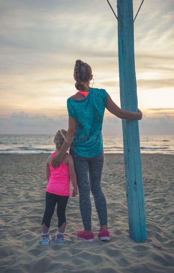 Bakifrån en moder och en dotter i konditionkugghjul på stranden royaltyfri bild