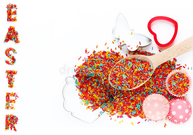 Baking background with ingredEaster baking ingredients - colorful sugar sprinkles, cookie cutters, paper tins for cake isolated o stock photos