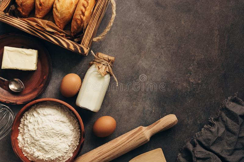 Baking background, ingredients for cooking pies, flour, butter, milk, eggs. Traditional Russians baked patties, pirozhki. Overhead stock photography